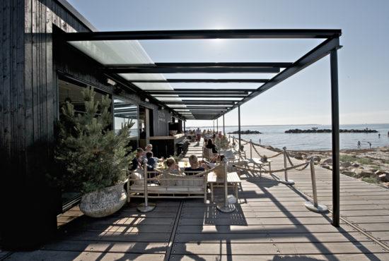 Glastaket över den välkända restaurangen Sillen & Makrillen i öppnat läge en varm sommardag. Alla glasluckor skjuts bak mot fasaden med det motoriserade systemet.